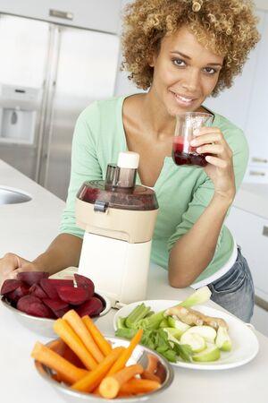 licuadora: La mujer adulta mediados de jugo de verduras frescas