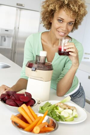 Mid Adult Woman Making Fresh Vegetable Juice photo