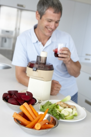 Middle Aged Man Making Fresh Vegetable Juice photo