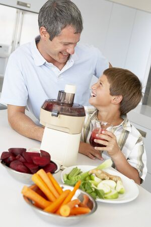 Father And Son Making Fresh Vegetable Juice photo