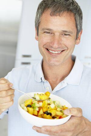 fruit salad: Middle Aged Man Eating Fresh Fruit Salad