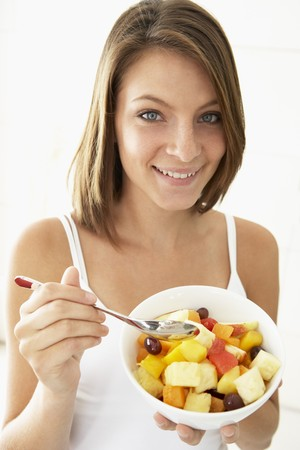 Young Woman Eating Fresh Fruit Salad photo