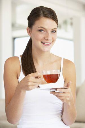 personas tomando cafe: Mujer joven Drinking t� herbal  Foto de archivo