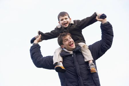 having fun in winter time: Father Carrying Son On His Shoulders
