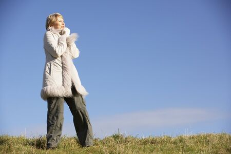 shivering: Senior Woman Standing In Park Stock Photo