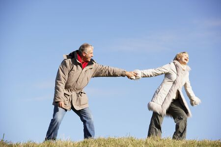 persuading: Senior Man Pulling His Wife By The Hand Stock Photo