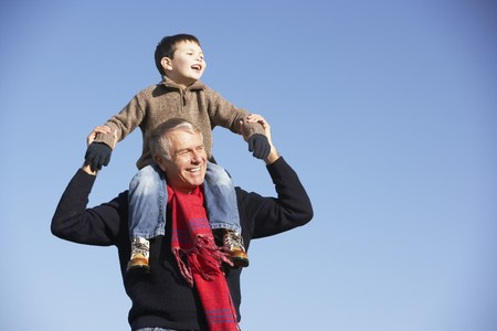 Grandfather Carrying Grandson On His Shoulders photo