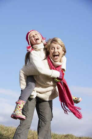 6 year old children: Grandmother Giving Her Granddaughter A Piggy Back Ride