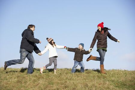 6 year old children: Family Running In The Park Stock Photo