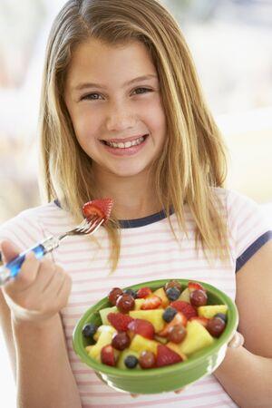 ni�a comiendo: Muchacha comer ensalada de frutas frescas