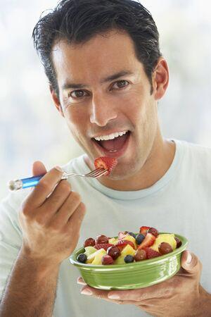 man eten: Mid volwassenen Man Eating Fresh Fruit salade