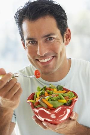 mid adult man: Mid Adult Man Eating Salad Foto de archivo