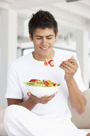 enjoyment: Young Man Eating A Salad Stock Photo