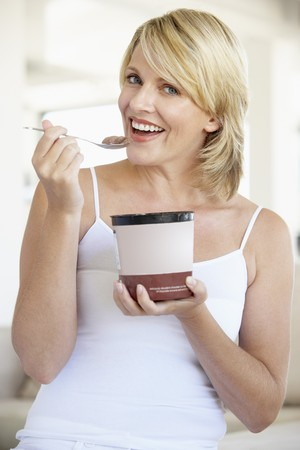 Mid Adult Woman Eating Chocolate Ice-Cream And Smiling At The Camera photo