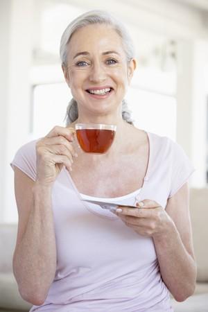 Senior Woman Holding Tea And Smiling At The Camera photo