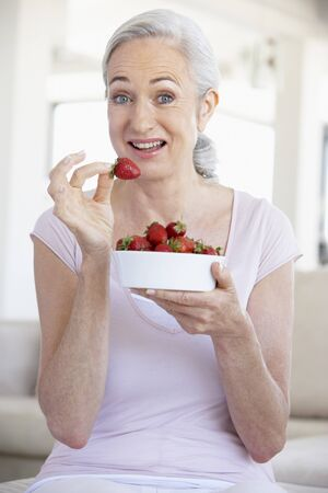 Senior Woman Eating A Bowl Of Strawberries photo