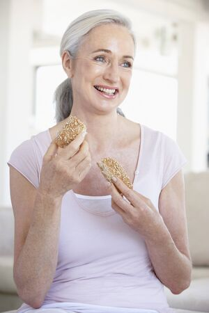 Senior Woman Eating Brown Bread Roll Stock Photo - 4513791