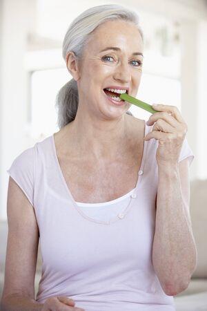 Senior Woman Eating A Celery Stick photo