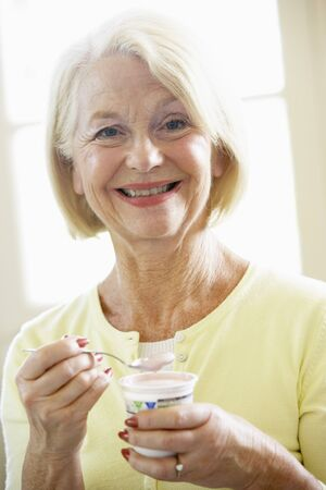 Senior Woman Eating Yogurt photo