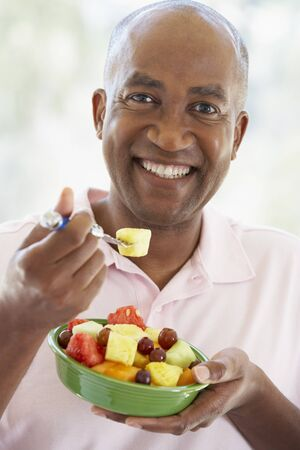 Middle Aged Man Eating Fresh Fruit Salad photo