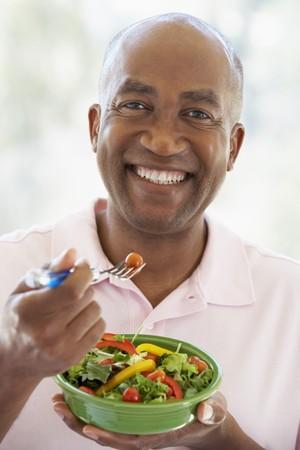 hombre comiendo: El hombre de mediana edad comiendo una ensalada Foto de archivo