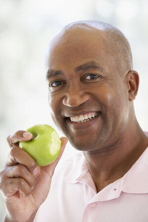 granny smith apple: Middle Aged Man Eating Green Apple And Smiling At The Camera Stock Photo