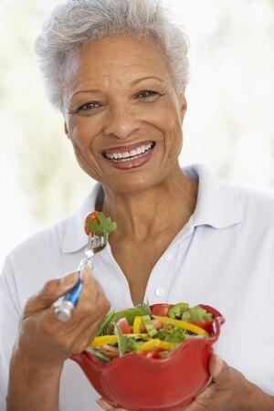 1 senior: Senior mujer comiendo una ensalada verde fresca