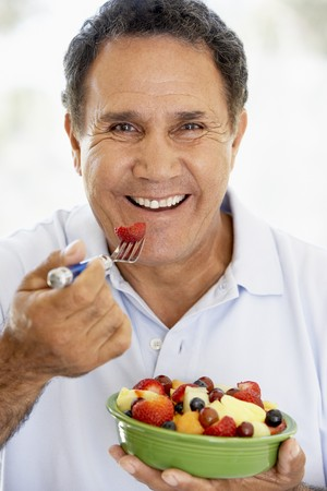 comiendo feliz: Senior Man Eating Fresh Fruit Salad