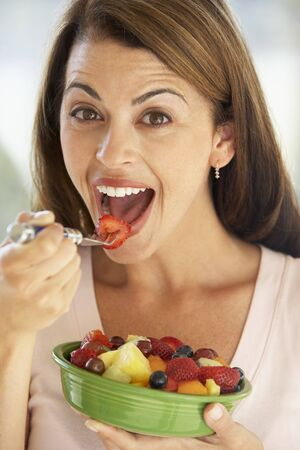 Mid Adult Woman Eating A Fresh Fruit Salad photo