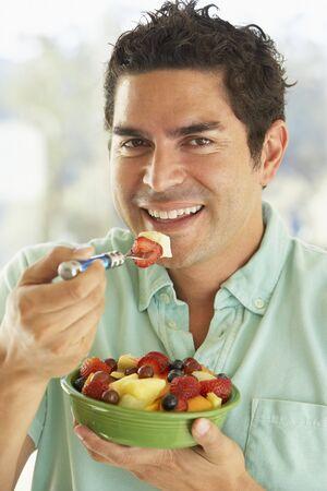 salade de fruits: Milieu homme adulte tenant un bol de salade de fruits frais, sourire � la cam�ra Banque d'images