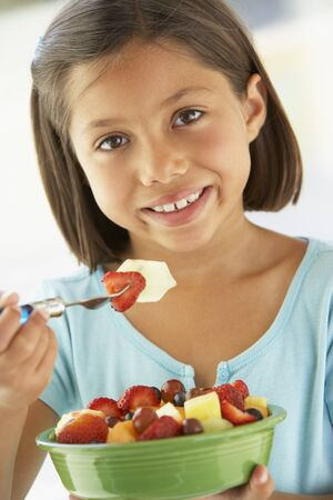 salade de fruits: Fille de manger un bol de salade de fruits frais