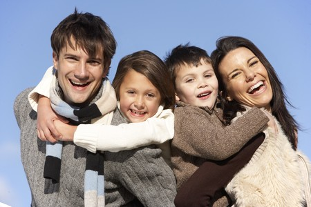 Parents Piggy Backing Their Children Stock Photo - 4513906