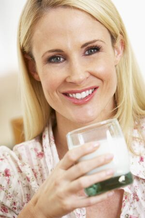 Mid Adult Woman Holding Glass Of Milk, Smiling At Camera photo