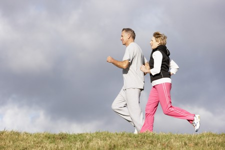 Senior Couple Jogging In The Park Stock Photo