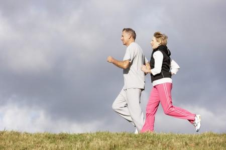 personas trotando: Senior pareja jogging en el Parque Foto de archivo