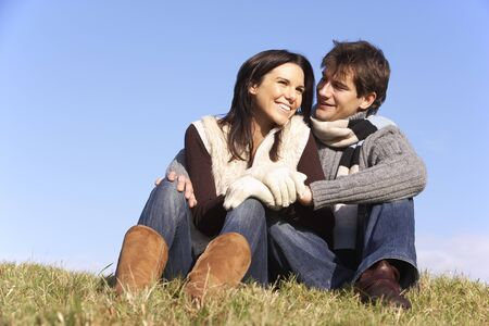 sit around: Couple Sitting In Park Together