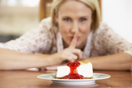 sneaking: Mid Adult Woman Looking At Cheesecake