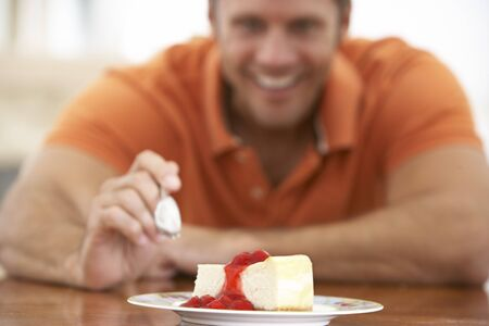 Middle Aged Man Eating Cheesecake photo