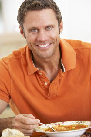 Middle Aged Man Eating Soup, Smiling At The Camera Stock Photo - 4546299