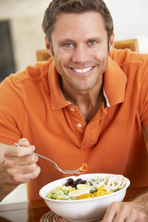 Middle Aged Man Eating A Healthy Meal, Smiling At The Camera photo