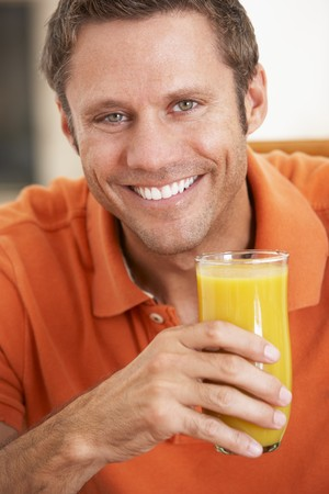 Middle Aged Man Drinking Fresh Orange Juice photo