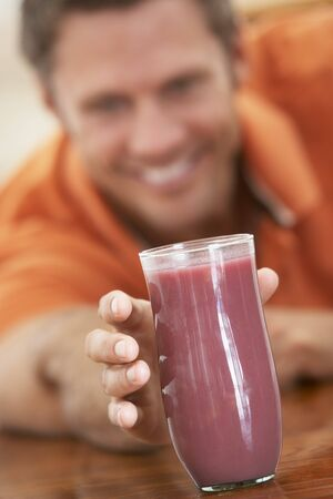 Middle Aged Man Drinking Fresh Berry Smoothie photo