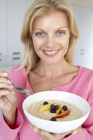 oatmeal: Mediados Woman adulta comer porridge con frutas  Foto de archivo