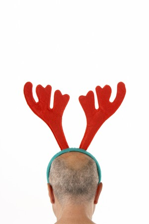 dressing up costume: Man Wearing Reindeer Antlers Against White Background Stock Photo