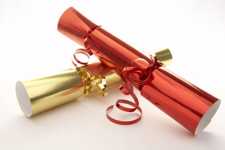 Red And Gold Christmas Crackers Against White Background photo