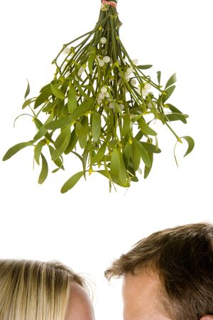 with mistletoe: Couple Standing Beneath Mistletoe Against White Background