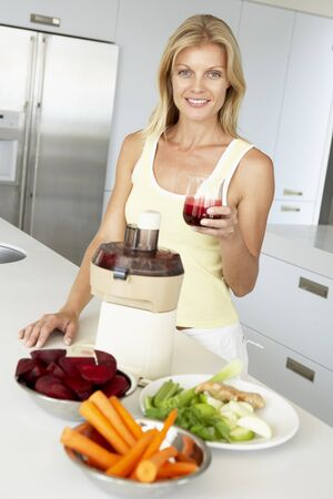 Mid Adult Woman Making Fresh Vegetable Juice Stock Photo - 4546656