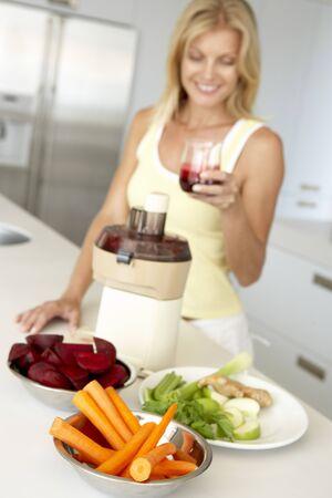 Mid Adult Woman Making Fresh Vegetable Juice Stock Photo - 4546443