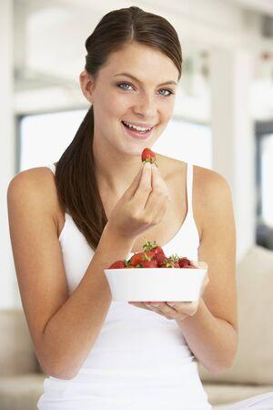 Junge Frau Essen eine Schüssel mit frischen Erdbeeren Lizenzfreie Bilder - 4546696
