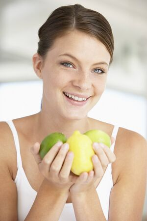 Young Woman Holding Fresh Fruit And Smiling At The Camera photo